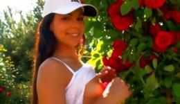 Teen beauty walking around with roses and she is touching her fine body