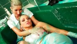 Two sassy bitches are getting all dirty in green stuff in a bathtub