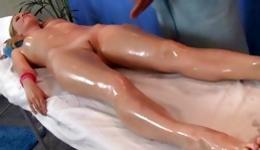 Lovely blonde lying on the massage table getting oiled body massaged