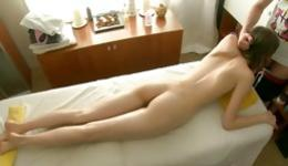 Skinny brunette lying on massage bed blowing tough dick hard core